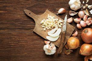 tabla de cortar con ajos y cebolla